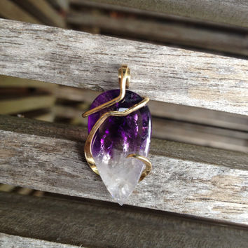 amethyst cut and polished and tension set in hand forged polished 14 karat gold