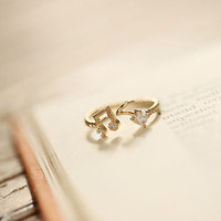 A tiny Gold plated music symbol multtask ring above by windcompany
