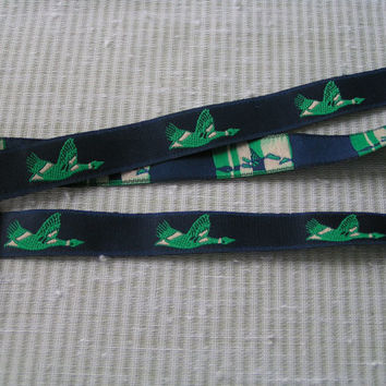 Flying Duck on Navy Blue Jacquard Ribbon, Green and White Duck on the Wing looks like he is against a dark sky. 5/8 inches wide