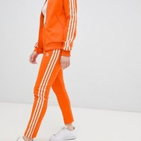 Adidas Originals Three Stripe Cigarette Pants In Orange at asos.com