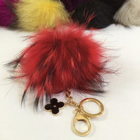 Fur pom pom keychain, bag pendant with flower charm in red with black markings color tone