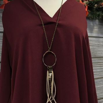 long necklace with wire hoop, stones, tree pendant, and tassels