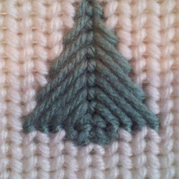 Christmas holiday stocking magnet with a tree raffia bow and pine cones made from plastic canvas and yarn