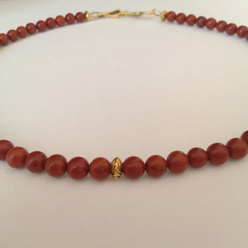 handmade necklace of red jasper pearl of 6 mm and gold colored spacer