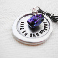 Live in the moment stamped silver necklace with bright purple swarovski heart.