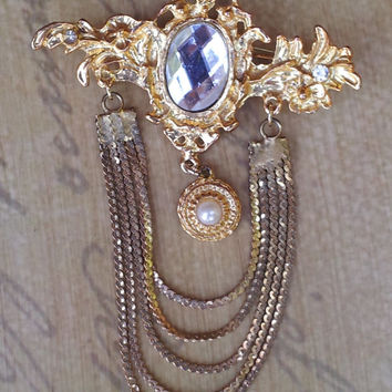 Gold tone brooch features a rhinestone studded pin and ornate dangling pendant with a large centeral cabochon