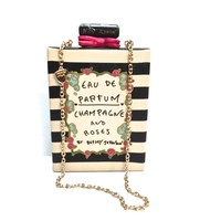 "Add some elegance to your look with Betsey's Parfum-shaped silhouette handbag, featuring cream/black stripe print throughout and ""EAU DE PARFUM CHAMPAGNE AND ROSES BY BETSEY JOHNSON"" written on front. Push lock closure with fuchsia color bow detailing, and"