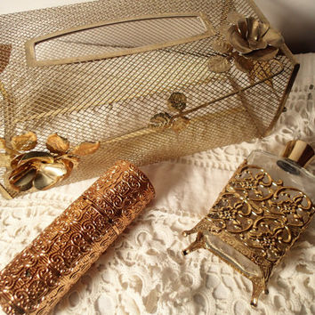 Gold metal vanity accessories, gold mesh tissue box, gold filigree perfume bottle, Embossed gold Caron Nuit de Noel spray container.