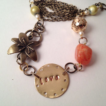 Gold hand stamped love necklace orange beads and flower clasp
