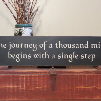 The journey of a thousand miles begins with a single step wood sign