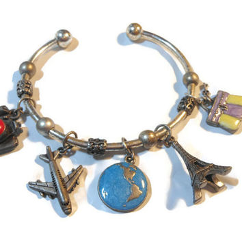 Avon travel charm cuff bracelet marked nr (made for Avon) silver plate with pewter charms - camera, plane, globe, Eiffel Tower, briefcase