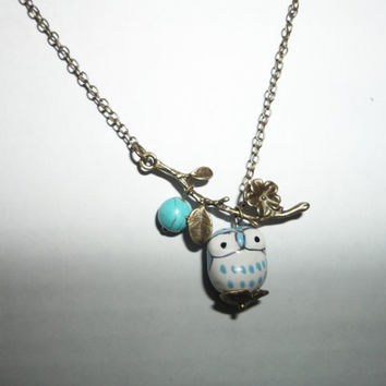 Ceramic blue owl with turquoise bead on a branch by grimspot