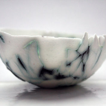 Stoneware English fine bone china small bowl with broken pieces and cracks with copper oxide.
