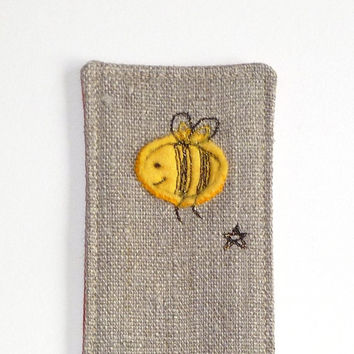 Bee bookmark on natural linen with orange and red spotty fabric back. Handmade embroidered bookmark with cute bee design. Made in England.