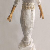 A gourd doll in white velveteen and chain on a wood base