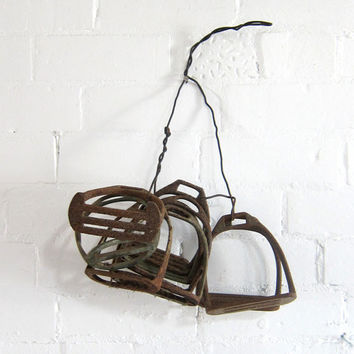Vintage collection of horse stirrups for rustic or industrial decor.