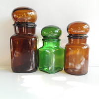 Set of 3 Apothecary  glass jars with Plastic food seal.in colors green and amber. Belgian vintage.