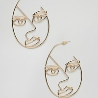 ASOS DESIGN hoop earrings with large abstract face in gold at asos.com