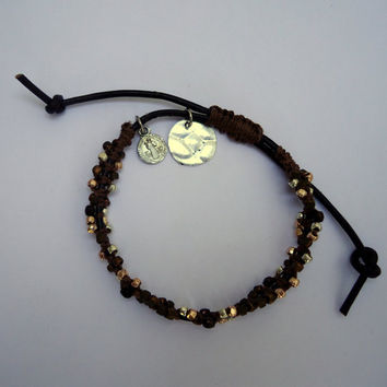 Macrame bracelet wrapped around brown leather cord with gold, copper and brown seed beads and hanging charms