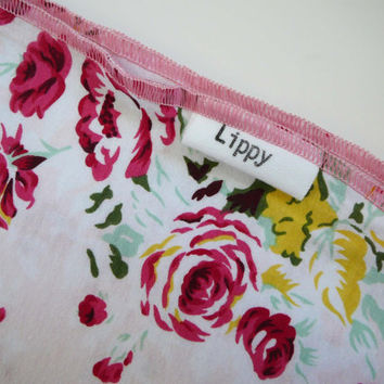 Girl baby blanket. Size 31 by 40 inches. Floral print with pink edging. Soft and stretchy knit fabric.