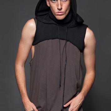 This unisex sleeveless badlands duster hoodie features ribbed knit harness-like top with a lightweight blended rayon knit fabrication hoodie, turtleneck/cowl neckline, adjustable drop cords, and crop hemline.