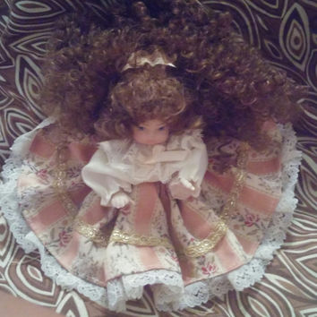 Adorable Tiny Porcelain Doll With Long Brown Curly Hair and Pink Dress With White Ruffles