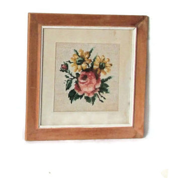 Vintage framed floral embroidery. Roses needlepoint. Cross stitch. Colorful. Frame is light brown.