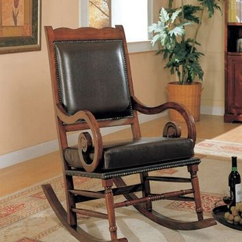 Mahogany finish wood and black bycast leather seat and back rocking chair with nail head trim and curved arms