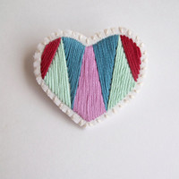 Embroidered heart brooch for Valentine's Day with geometric color block in emerald and mint greens with violet and red on cream muslin