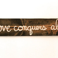 "Custom quote sign ""love conquers all"""