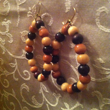 Wooden bead hoop earrings with a golden clasp.