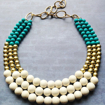 Turquoise, gold and ivory colored wooden beads. Make a statement in light weight wood necklace. 18 inches and a 2 inch extender of aluminum