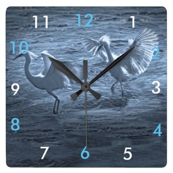 A bird chasing another bird, on a wall clock. square wallclock