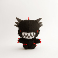 Black dragon plush with a scary expression and a cute heart