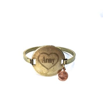 We would love to tell you a little bit about Top Shelf brand jewelry line so you may appreciate the wonderful handcrafted Engraved Army vintage brass locker tag cuff with a dainty copper color penny you are looking at! This is a costume jewelry manufacture