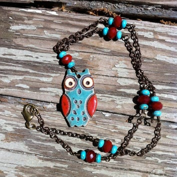 Handmade ceramic owl pendant by Kylie Parry on a brass chain with turquoise and red glass beads.